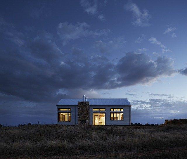 Malý domček s veľkými oknami uprostred lúky.jpg